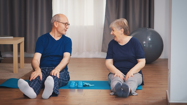 거실에 있는 요가 매트에 몸을 기지개하는 수석 부부. 집에서 노인 건강한 생활 방식 운동, 운동 및 훈련, 집에서 스포츠 활동