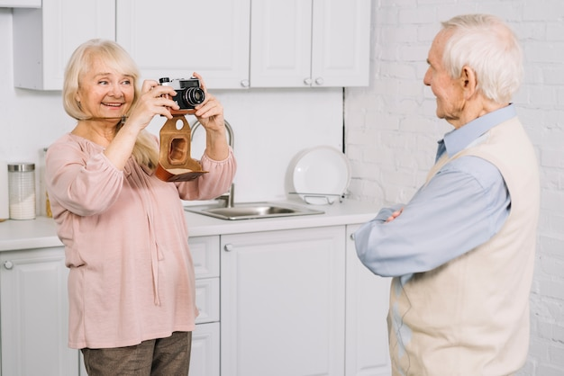 Senior couple taking photo in kitchen