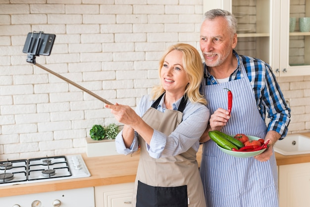 Senior couple taking selfie on mobile phone in the kitchen