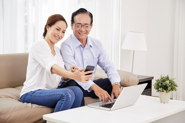 スマートフォンで自分撮りをしている年配のカップル
