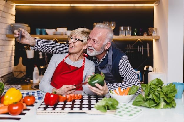 Старшие пары, делающие селфи фото, вместе готовят обед на кухне.