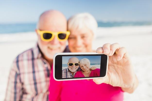 Senior couple taking selfie with smartphone
