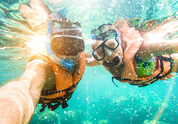 Senior couple taking underwater selfie snorkeling in tropical sea excursion with water camera