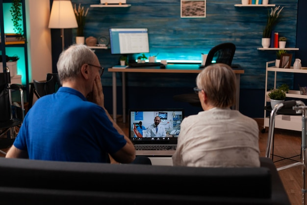 Senior couple talking on video call with dentist using laptop