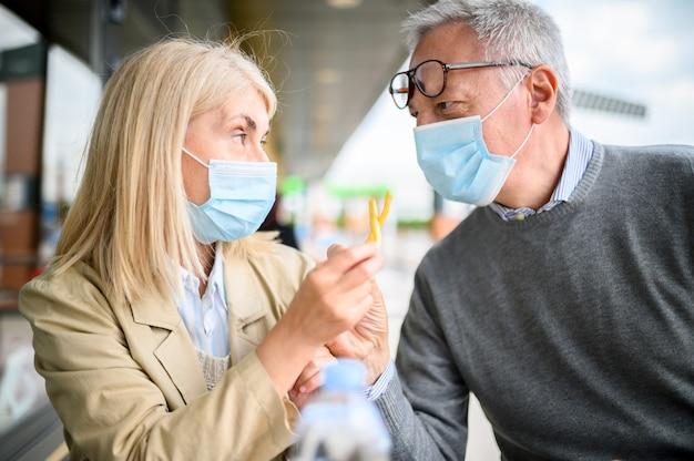 Пожилые супружеские пары жарят картофель фри в фаст-фуде и в масках