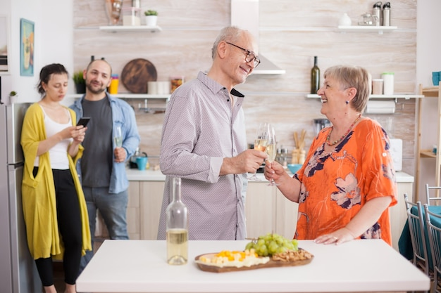 家族のブランチ中にキッチンでワイングラスを乾杯する年配のカップル。様々なチーズの前菜。老人と女性がお互いを見ています。