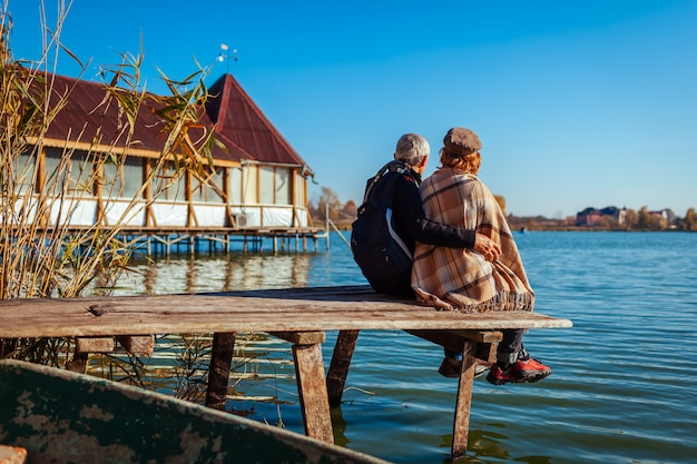 Senior couple of tourists relaxing by autumn lake. happy man and woman enjoying nature and hugging sitting on pier
