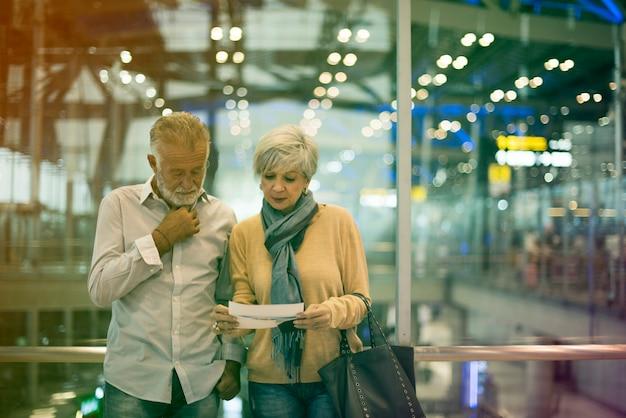 Старшая пара путешествует в аэропорту