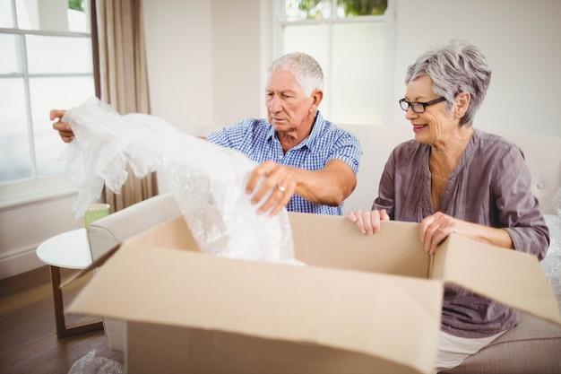 Senior couple unpacking a cardboard box in living room