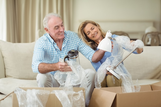 年配のカップルがリビングルームで段ボール箱を開梱