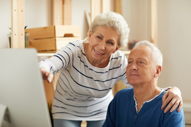Пожилая пара с помощью компьютера