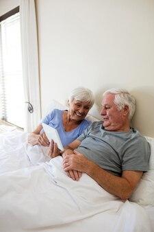 Старшая пара с помощью цифрового планшета в спальне дома