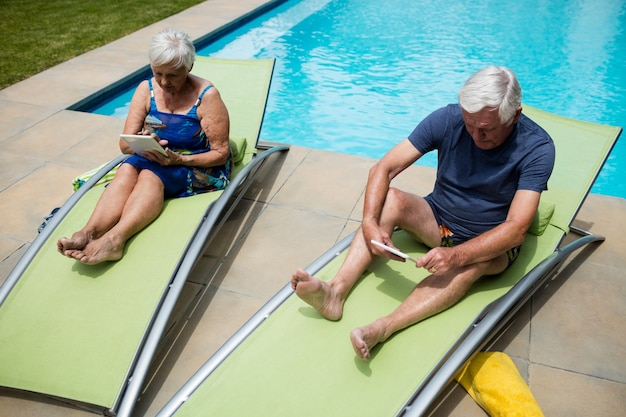 Senior couple using digital tablet on lounge chair at poolside
