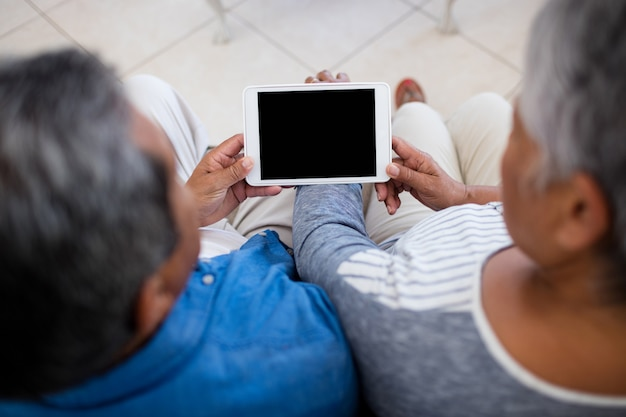Senior couple using digital tablet while sitting in the living room