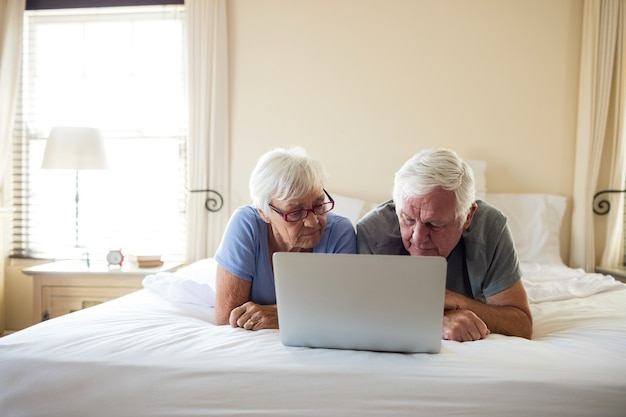 Senior couple using laptop on bed in bedroom at home