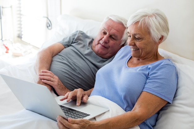 Senior couple using laptop in the bedroom at home
