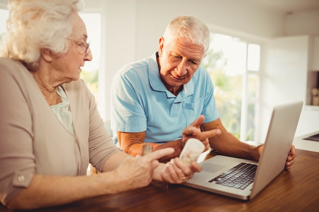 Senior couple using laptop and holding pills at home