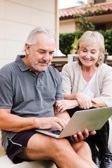 年配のカップルが庭でラップトップを使用して