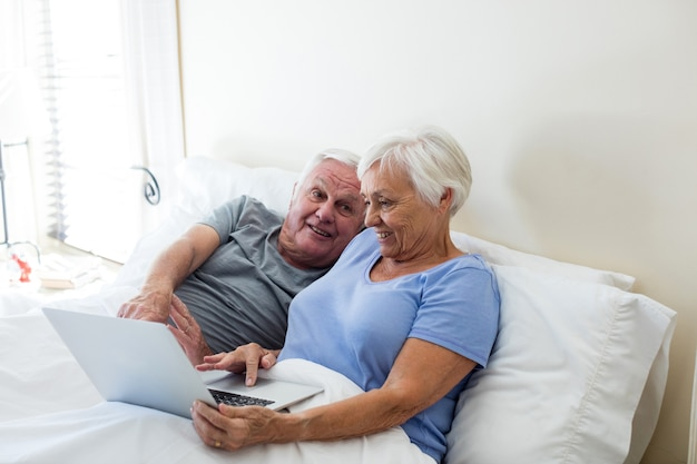 自宅の寝室でラップトップを使用している年配のカップル