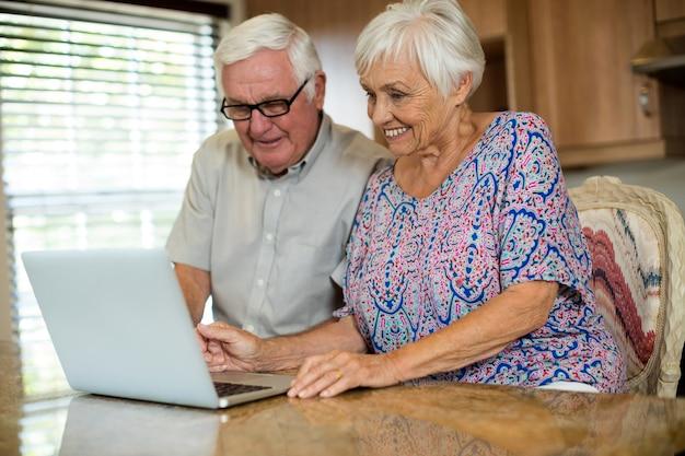 Старшая пара, использующая ноутбук на кухне дома