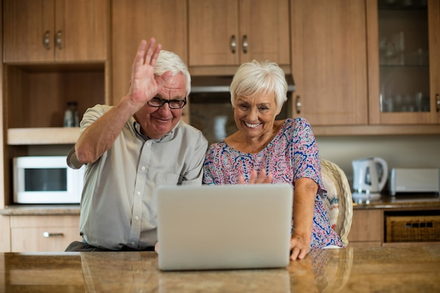Senior couple using laptop in the kitchen at home