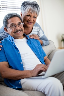 Senior couple using laptop in living room at home