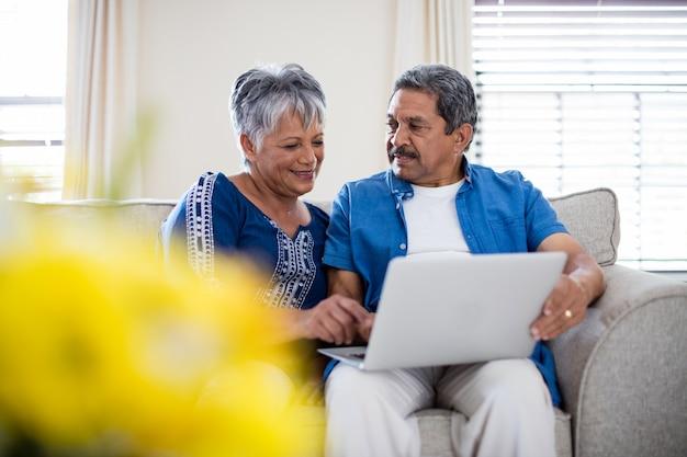 Senior couple using laptop in living room