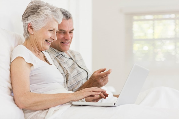 Senior couple using laptop sitting on the bed
