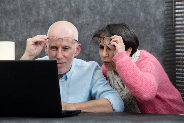 Senior couple using laptop, they having difficulties and vision problems