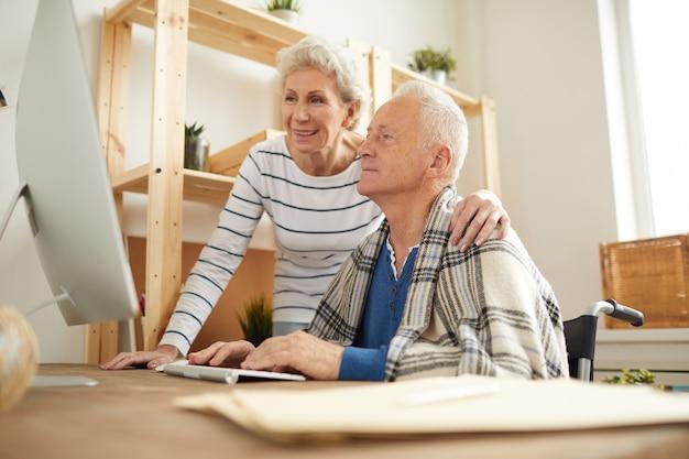 Пожилая пара с помощью пк