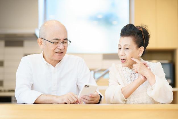 Senior couple using smartphones through trial and error in the room