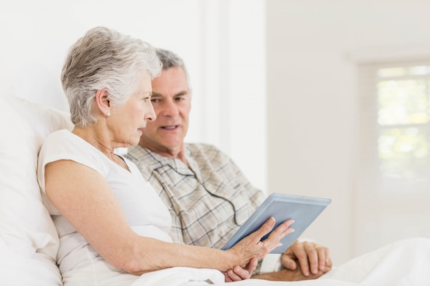 Senior couple using tablet sitting on bed