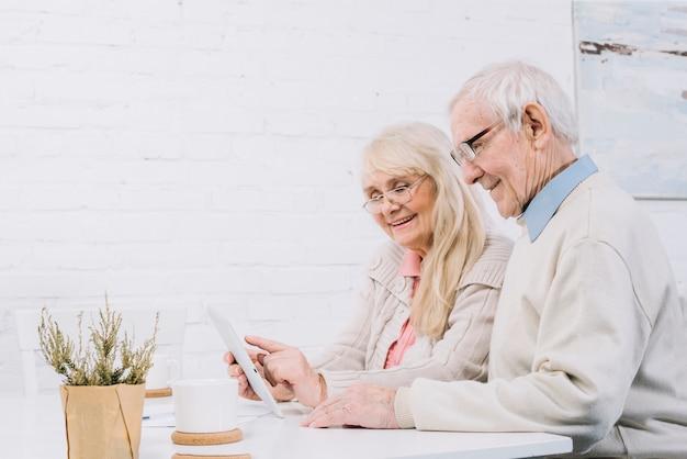 Пожилая пара с помощью планшета