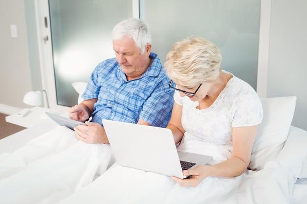 Senior couple using technologies on bed