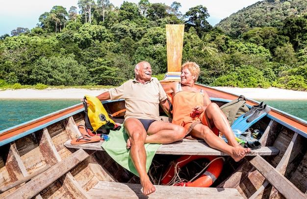 Пожилая пара отдыхает в туре по острову после исследования пляжа во время прогулки на лодке с маской и трубкой в таиланде