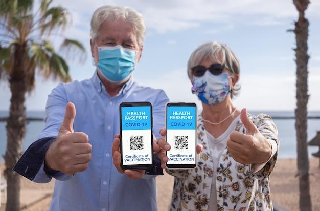 Senior couple vaccinated against coronavirus contagion show health passport of vaccination certificate