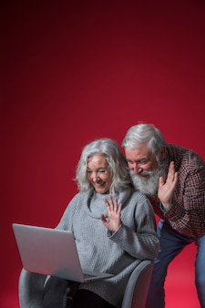 Senior couple video chatting on laptop waving their hands against red background