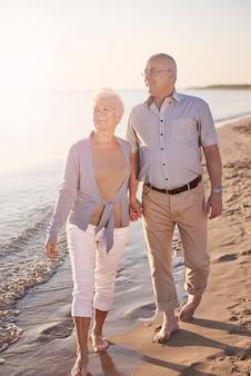 해변을 가로 질러 걷는 수석 부부