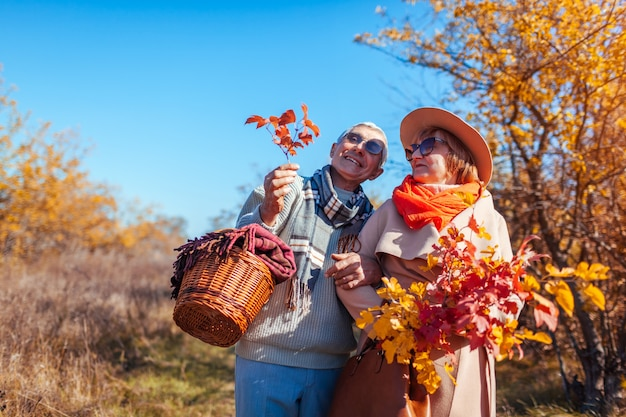 Senior couple walking in autumn forest hugging and chilling outdoors
