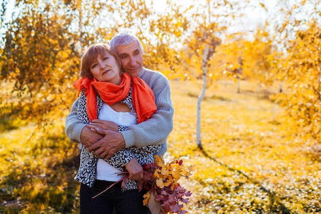 Senior couple walking in autumn forest middle aged man and woman hugging