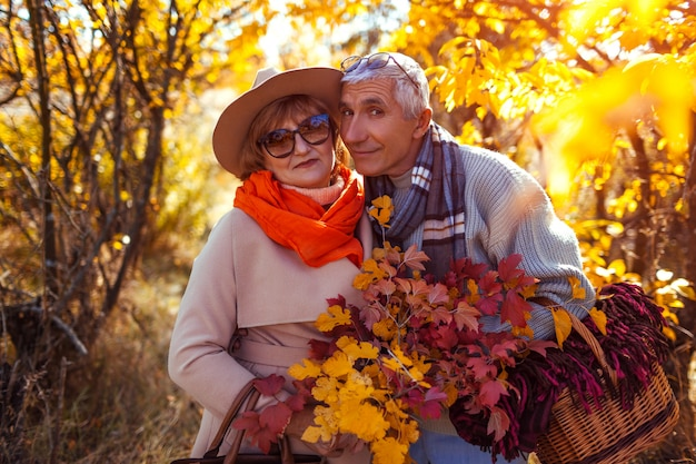 Senior couple walking in autumn forest.
