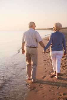 手で歩いている年配のカップル