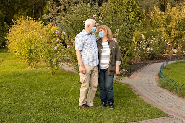 医療マスクを身に着けている春または夏の公園を歩く年配のカップル