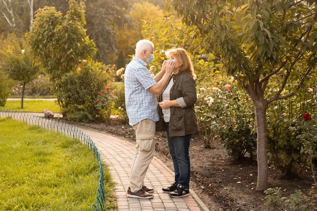 Senior couple walking outside wearing medical masks