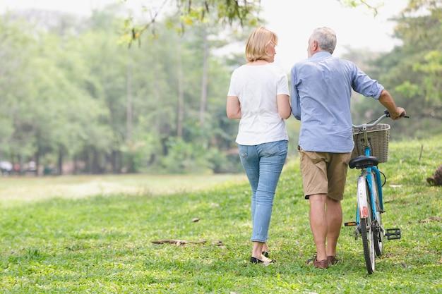 Senior couple walking their bike