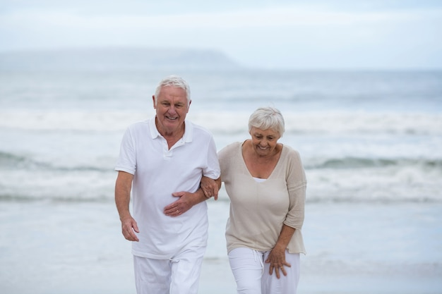 Senior couple walking together on the beach