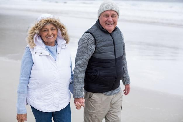 Senior couple walking toward the ocean while holding hands