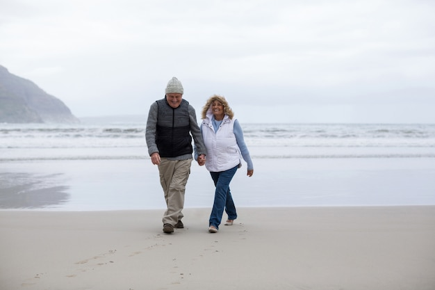 Senior couple walking with holding hands on the beach