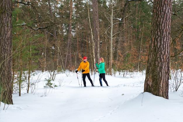 눈 덮인 겨울 숲에서 노르딕 워킹 폴과 함께 걷는 수석 부부