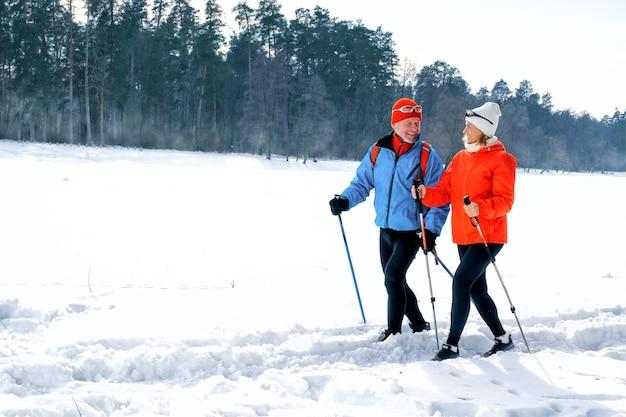 눈 덮인 겨울 공원에서 노르딕 워킹 폴과 함께 산책하는 수석 부부